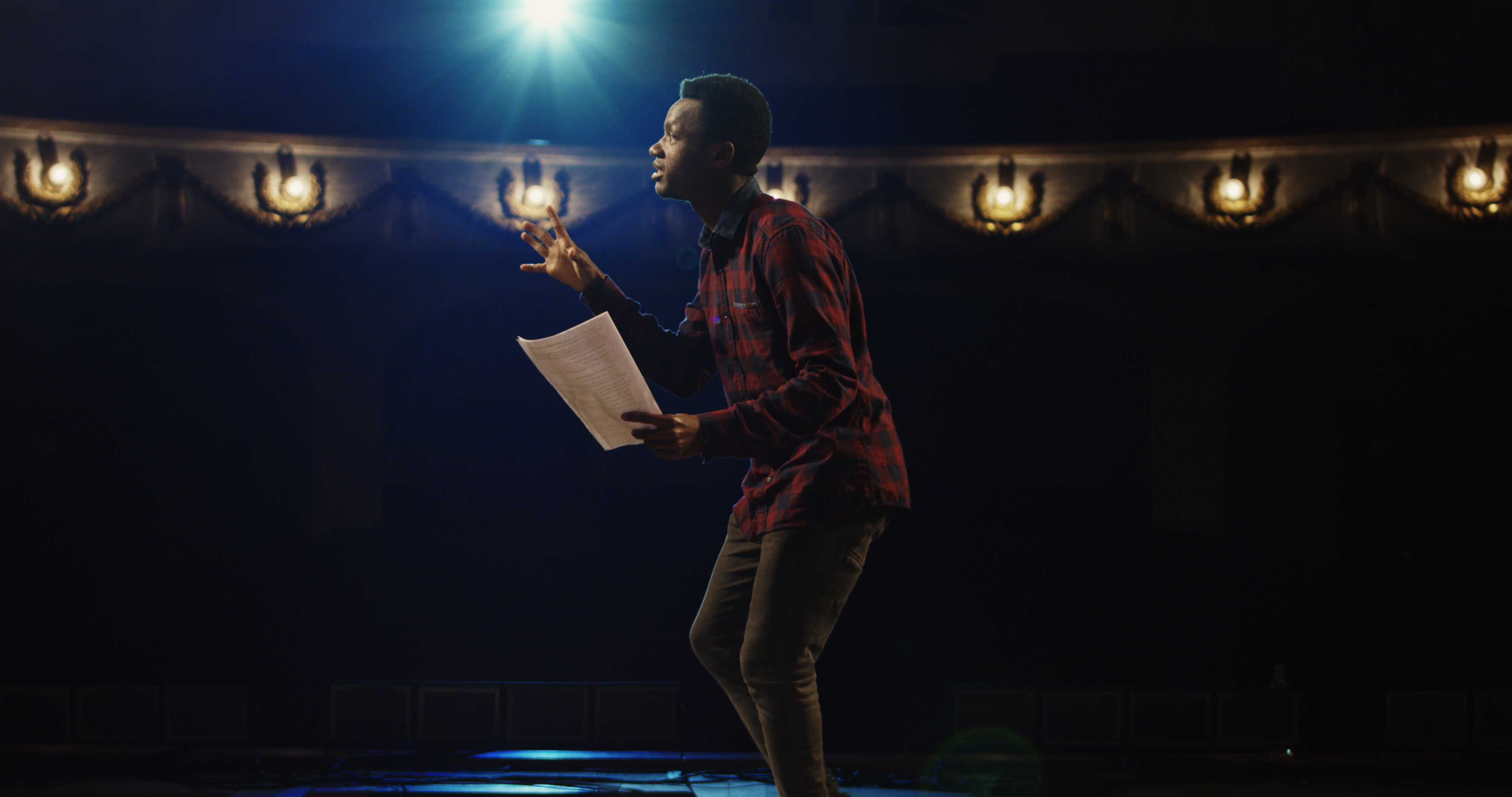 black male actor on stage with script in hand